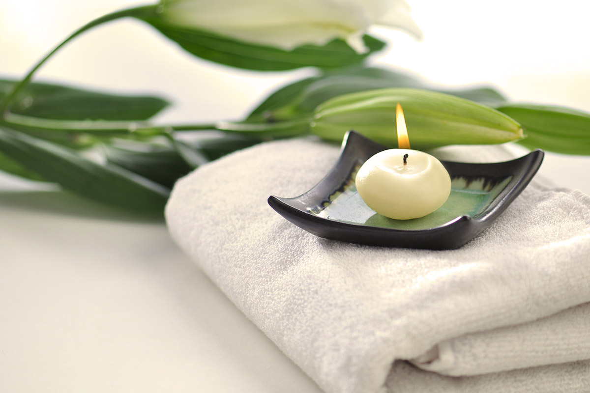 Scented candle and flowers placed on white towel