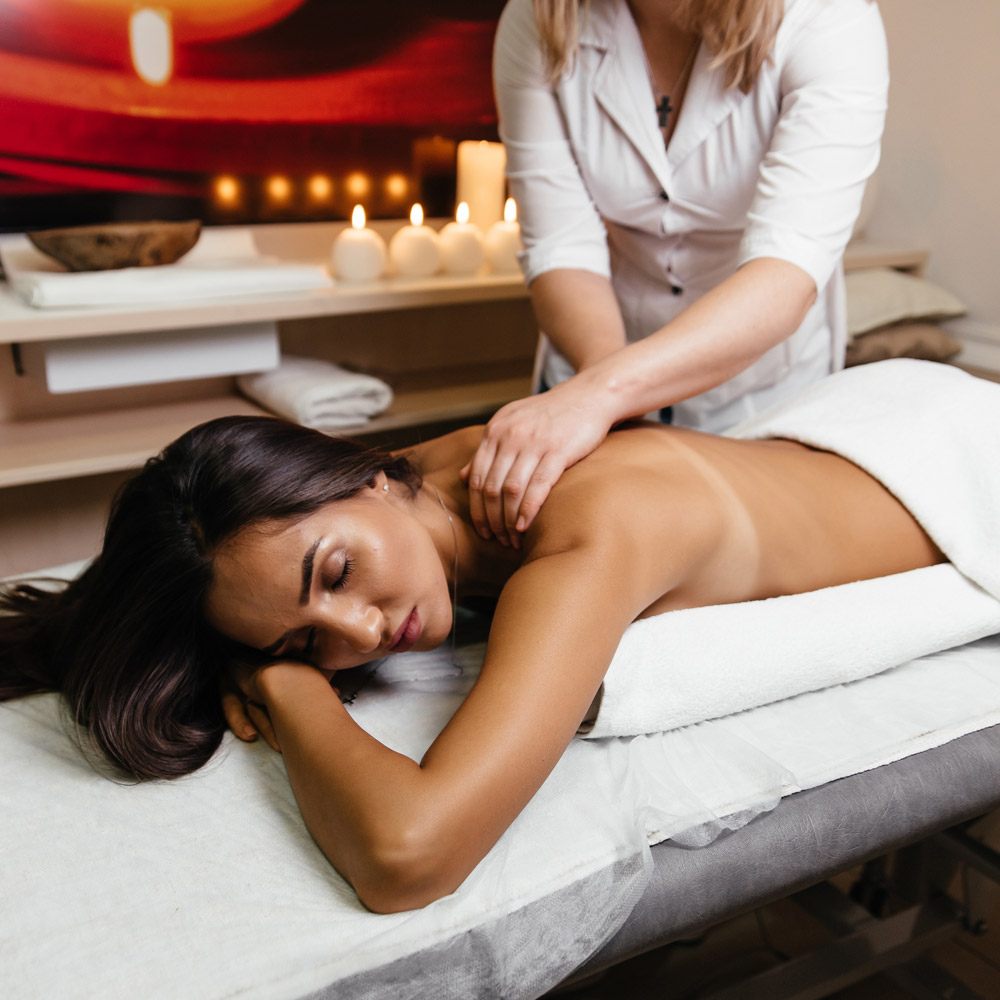 Young and healthy woman in spa salon - Traditional Swedish massage therapy and beauty treatments